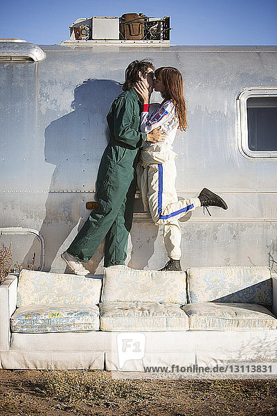 Young couple kissing while standing on sofa against trailer home on field