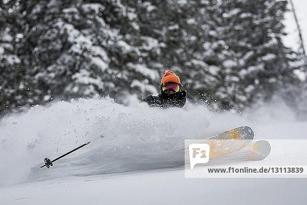 Mann fährt Ski auf schneebedeckter Landschaft