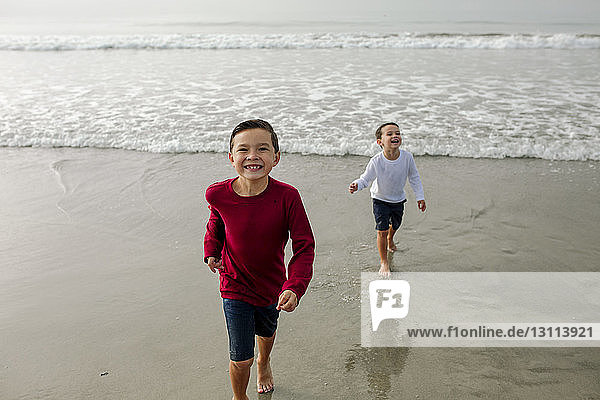 Portrait of cheerful boy with brother standing in background on shore