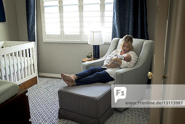 Mother carrying son while relaxing on chair against window at home