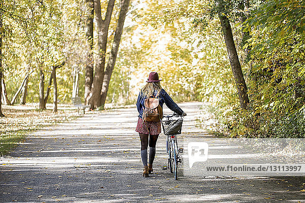 Rear view of woman with bicycle walking on road amidst trees