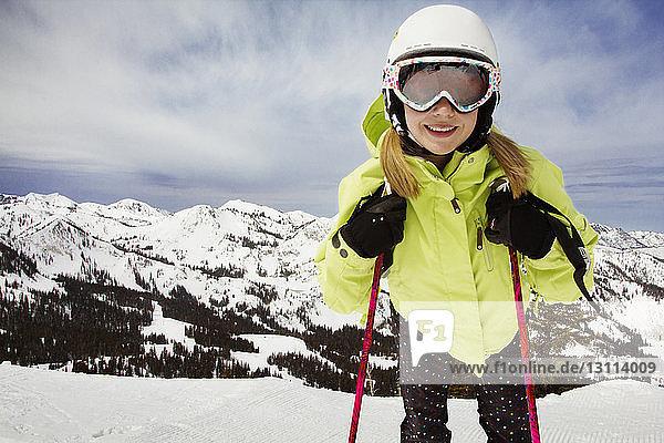 Glückliche Frau fährt auf schneebedecktem Feld gegen Berg