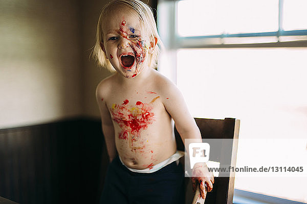 Boy with paint on face and body shouting while standing on chair