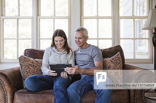 Happy teenage girl looking at tablet while sitting with grandfather on sofa at home