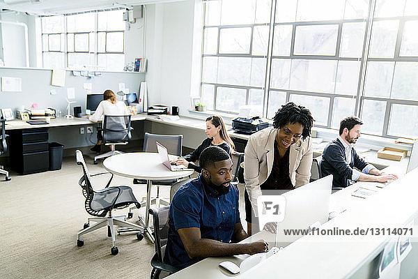 Geschäftsfrau  die einem Kollegen am Desktop-Computer zur Seite steht