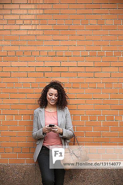 Glückliche Geschäftsfrau benutzt Smartphone  während sie an einer Ziegelmauer steht