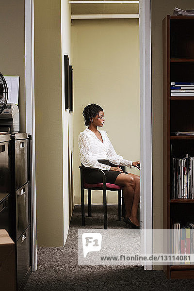 Woman sitting on chair at home seen through doorway