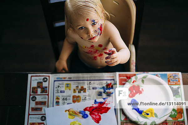 High angle view of boy painting while sitting at table