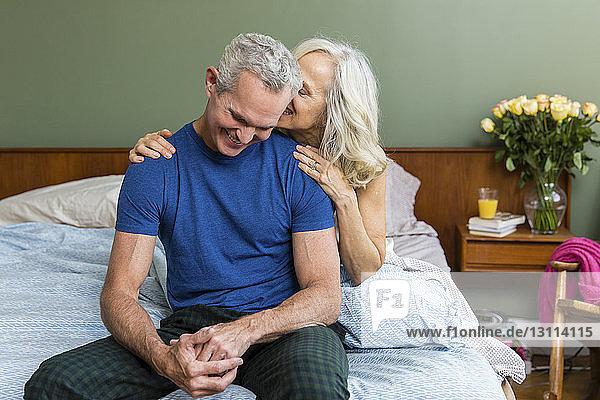 Glückliches Paar sitzt zu Hause im Bett
