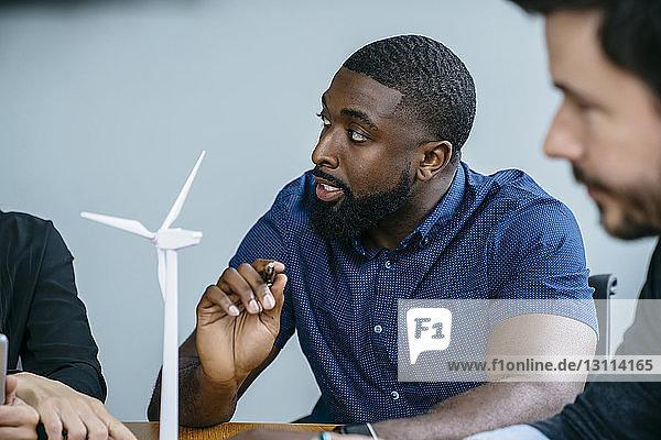 Geschäftsleute  die während einer Besprechung im Büro am Modell einer Windkraftanlage arbeiten