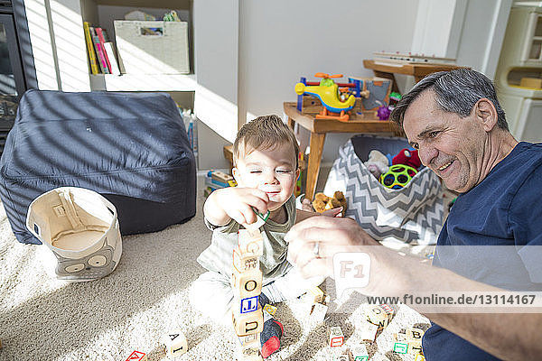 Happy grandfather and grandson playing with toy blocks in living room at home