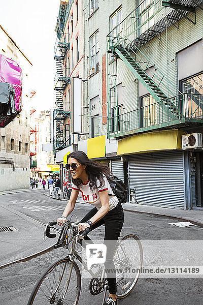 Glückliche Frau fährt Fahrrad auf Stadtstraße