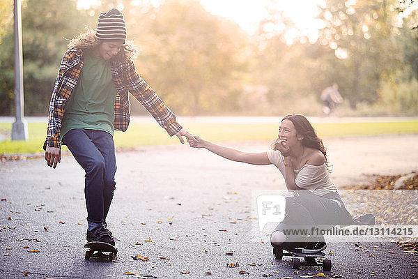 Paar hält sich beim Skateboarden auf der Straße an den Händen