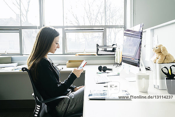 Businesswoman using smart phone while sitting on chair at desk in office