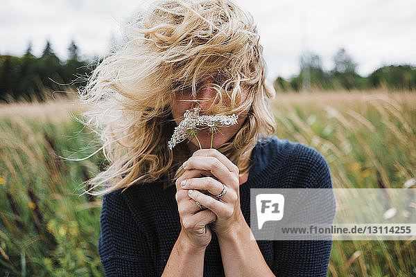 Woman with tousled hair holding flowers on field