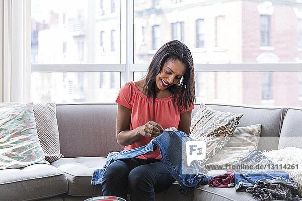 Glückliche Frau näht Textilaufnäher auf Jeans  während sie zu Hause auf dem Sofa am Fenster sitzt
