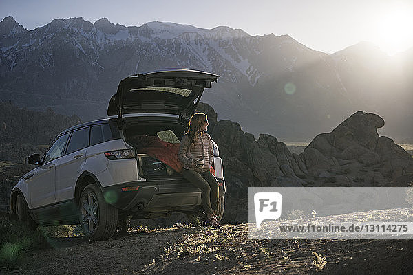 Female hiker looking away while sitting in car trunk against Alabama Hills
