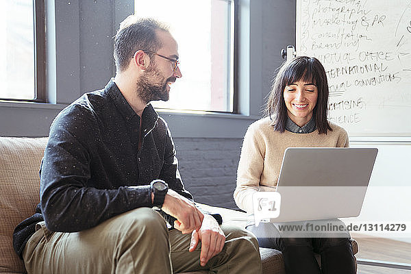 Man looking at businesswoman using laptop computer in office