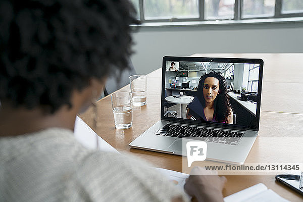 Businesswoman discussing with female colleague over video conference in board room