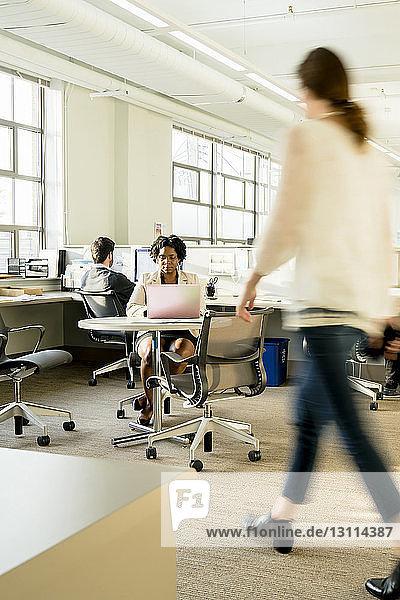 Verschwommene Bewegung einer Geschäftsfrau  die im Büro geht