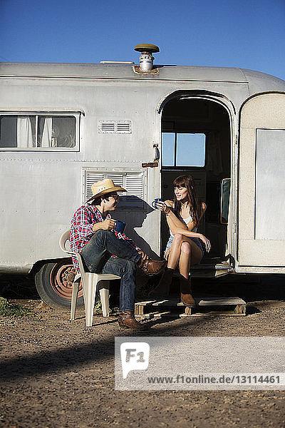 Ehepaar trinkt Kaffee  während es vor dem Wohnmobil sitzt