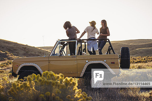 Female friends standing in off-road vehicle on field against clear sky