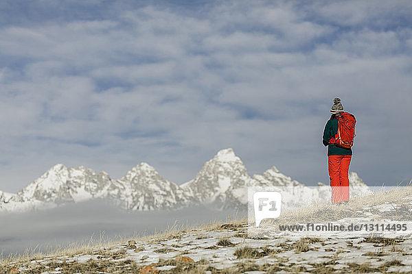 Wanderin mit Rucksack schaut auf die Aussicht  während sie vor schneebedeckten Bergen und bewölktem Himmel steht