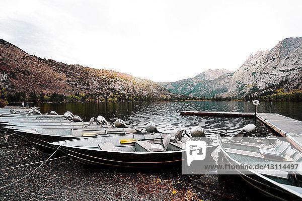 Boote vertäut am Flussufer durch Berge gegen klaren Himmel
