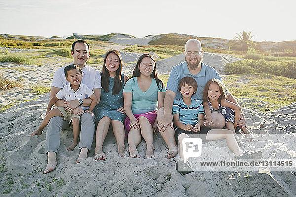 Portrait of family sitting on sand against sky