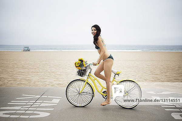 Side view of woman wearing bikini riding bicycle on street by beach