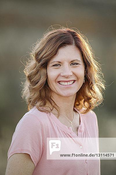 Bildnis einer lächelnden Frau im Wald stehend