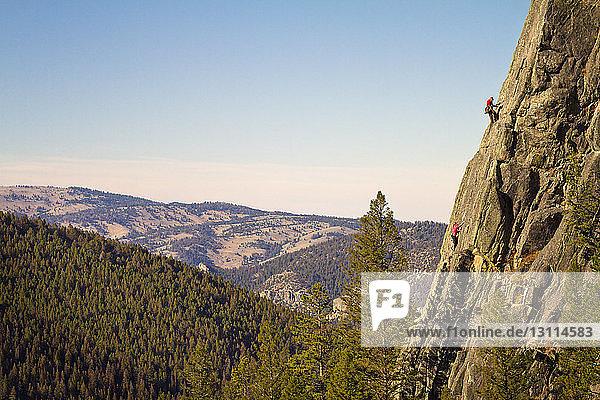 Bergsteiger klettern Berg für Berg durch Wald gegen klaren Himmel