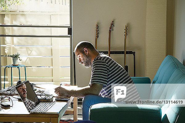Side view of man writing while sitting on sofa at home