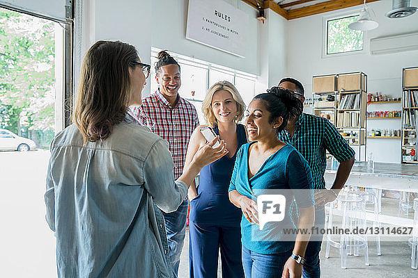 Geschäftsfrau zeigt glücklichen Kollegen im Büro Smartphone