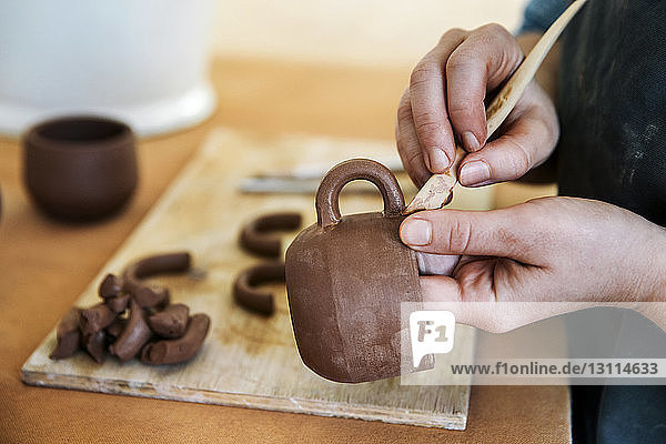 Close-up of woman's hands shaping earthenware