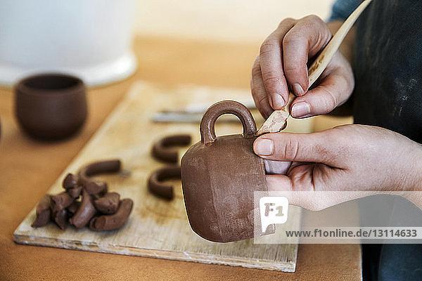 Nahaufnahme von Frauenhänden  die Steingut formen