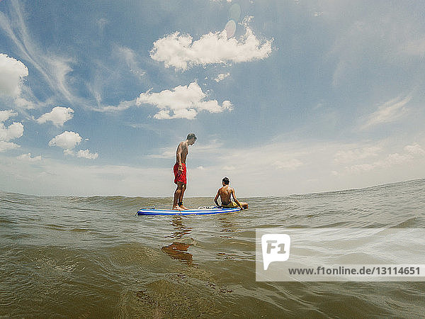 Shirtless brothers paddleboarding on sea against sky