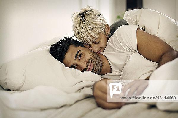 Porträt eines lächelnden Mannes  der mit einer liebenden Frau zu Hause im Bett liegt