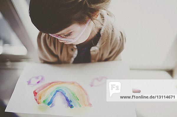 Süßes Mädchen betrachtet auf Papier gemalten Regenbogen