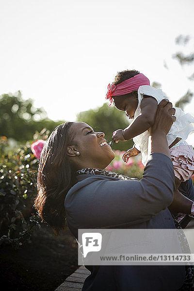 Nahaufnahme einer glücklichen Mutter  die ihre Tochter abholt  während sie bei Pflanzen im Park steht