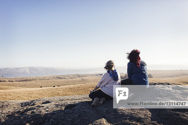 Mother and daughter looking at view while sitting on rocks against clear sky
