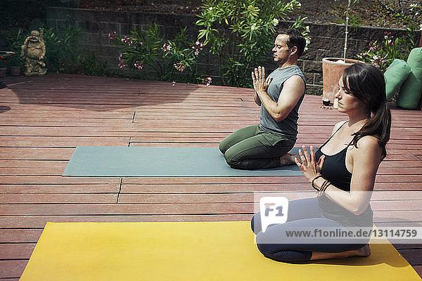 Hochwinkelansicht eines Paares  das auf Übungsmatten im Hinterhof Yoga macht