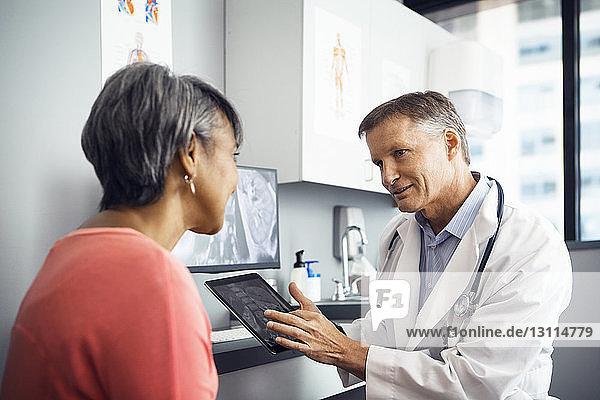 Männlicher Arzt erklärt dem Patienten in der Klinik das Röntgenbild am Tablet-Computer Männlicher Arzt erklärt dem Patienten in der Klinik das Röntgenbild am Tablet-Computer