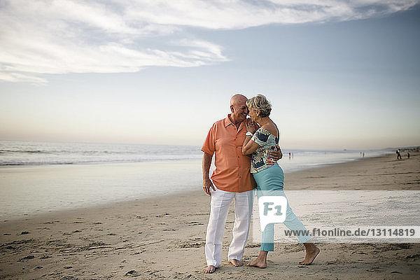 Romantisches älteres Ehepaar schaut sich an  während es am Meer gegen den Himmel steht
