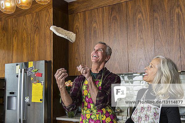 Fröhlicher Mann wirft Pizzateig  während eine Frau in der heimischen Küche das Essen zubereitet