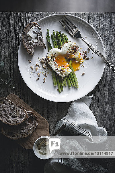 Overhead view of fried egg with asparagus and bread served in plate