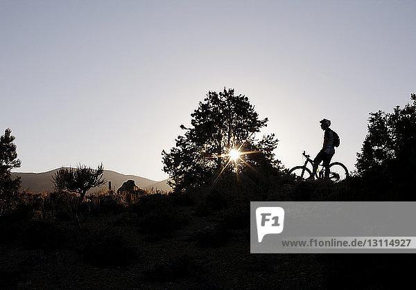 Scherenschnitt eines Mannes mit Fahrrad auf dem Feld vor klarem Himmel bei Sonnenuntergang