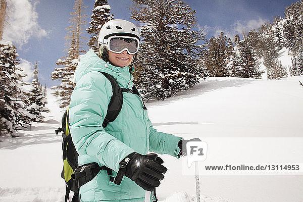 Glückliche Frau fährt auf schneebedecktem Berg gegen Bäume