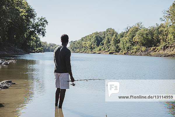 Rear view of man holding fishing rod while standing in lake against clear sky