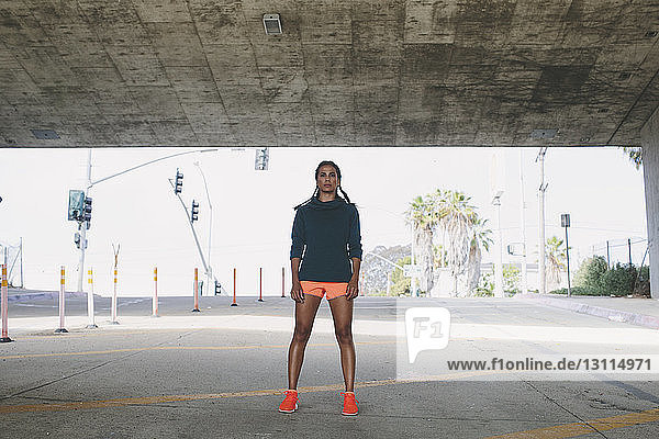 Confident woman standing at road under bridge